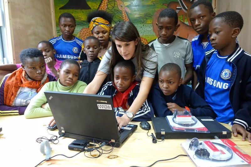 Woman explaining something to kids in a computer.