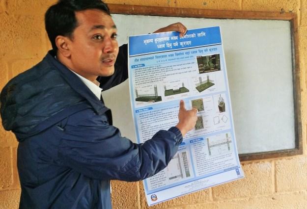 Er Ganesh Karmacharya shows phamplets related to earthquake safety