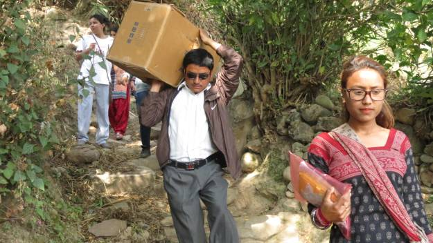 Program Officer Niroj Shrestha carries medicine box