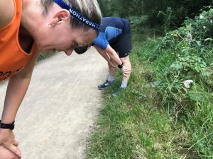 The joys of marathon training. Two runners bent over trying to catch their breath.