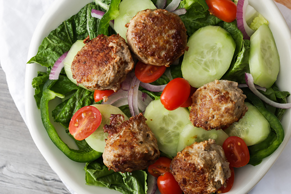 Salad with meatballs on top.