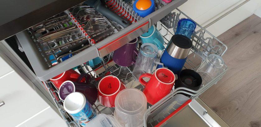 De afwas in de vaatwasser doen.