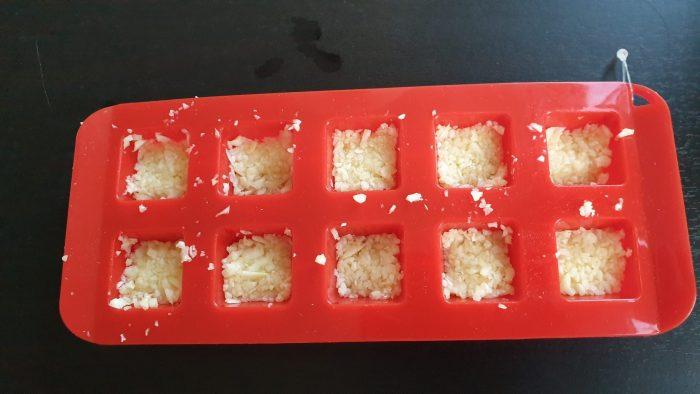 Fijngesneden knoflookteentjes in de kleine ijsblokjesvorm.