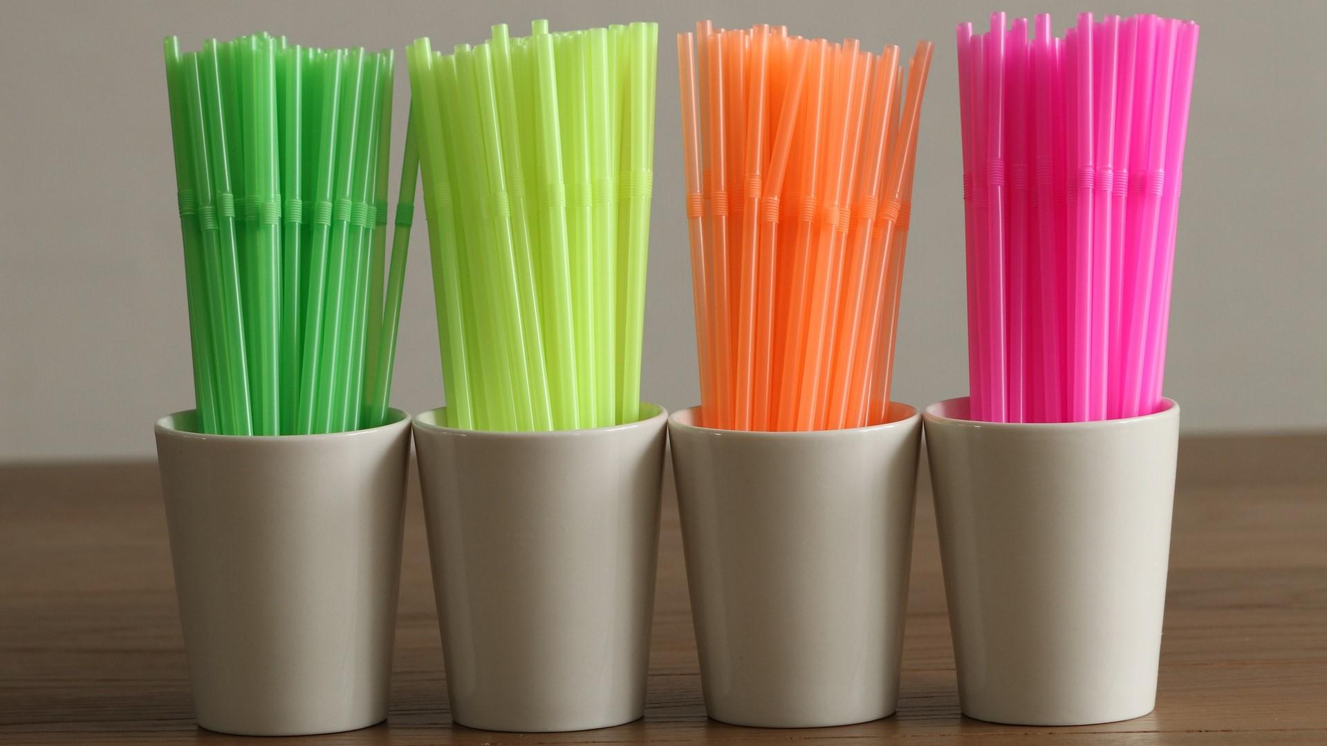 Groene, gele, oranje en roze rietjes in potten