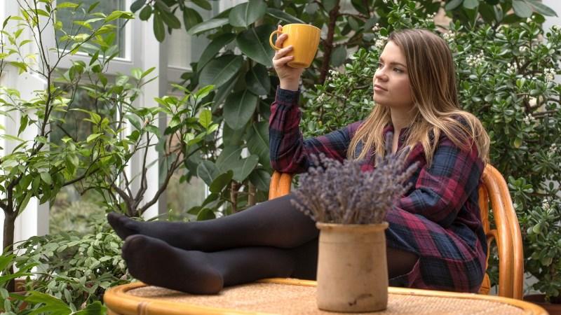 Een meisje lekker lui in de tuin met kopje koffie.