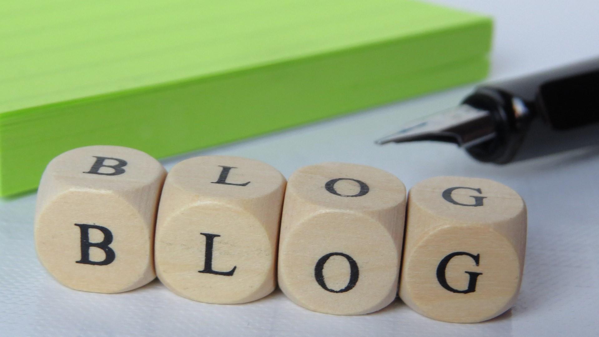 dobbelstenen die het woord blog vormen, een vulpen en een groen notitieblokje