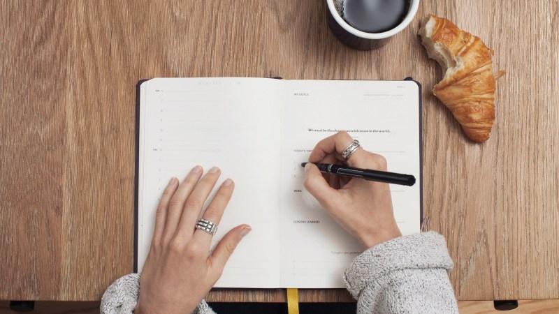 iets opschrijven in een notitieblok, met een kopje zwarte koffie en een croissant