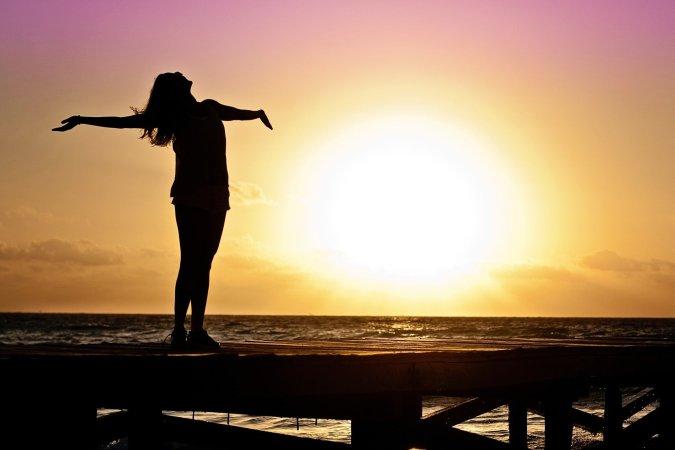 Vrouw met wie het heel goed gaat, strekt haar armen uit bij zonsondergang.
