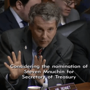 Senator Brown presses the questions gesturing with both hands