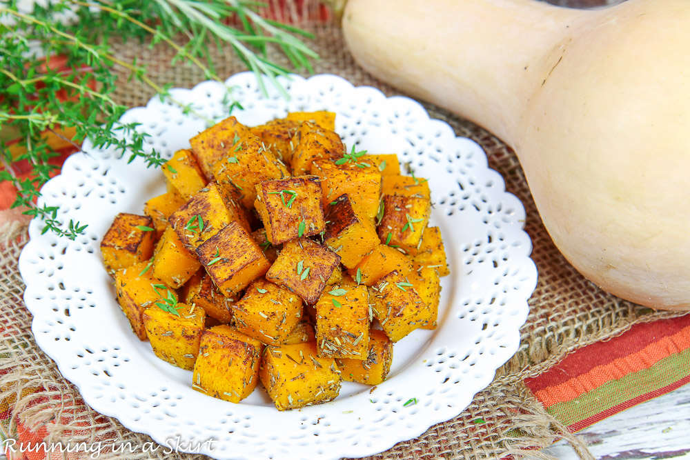 Oven Roasted Butternut Squash recipe on a white plate with a whole butternut squash.