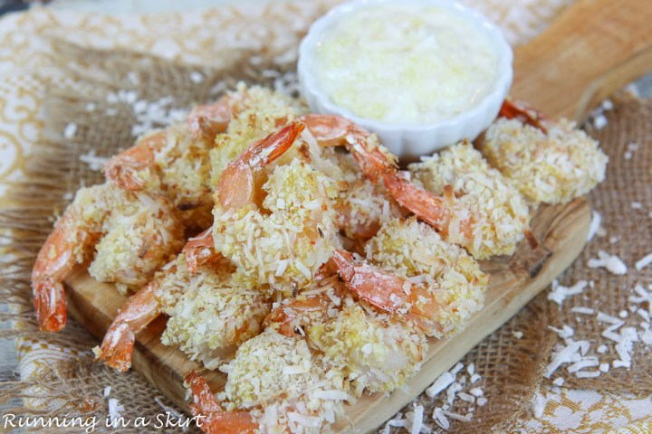 Oven Baked Coconut Shrimp piled on a wooden serving tray.
