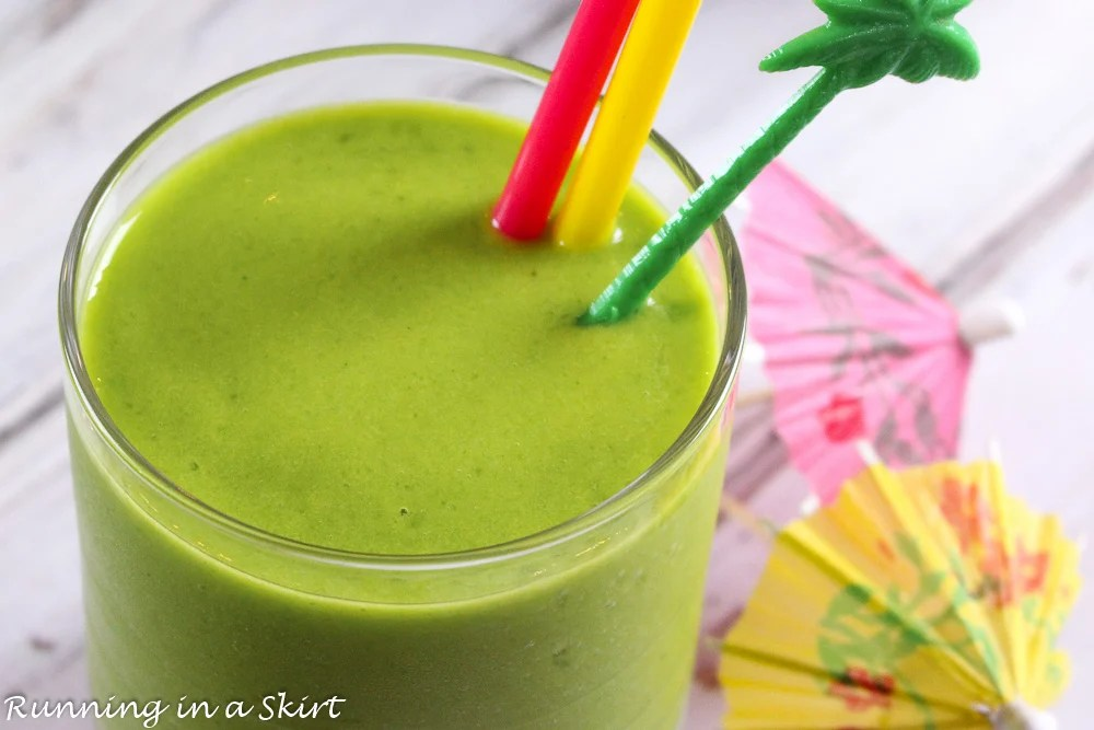 Close up of health green smoothie with a palm tree straw.