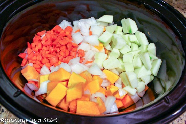 Butternut squash, carrots, apples and onion in a crock pot before the soup is cooked.