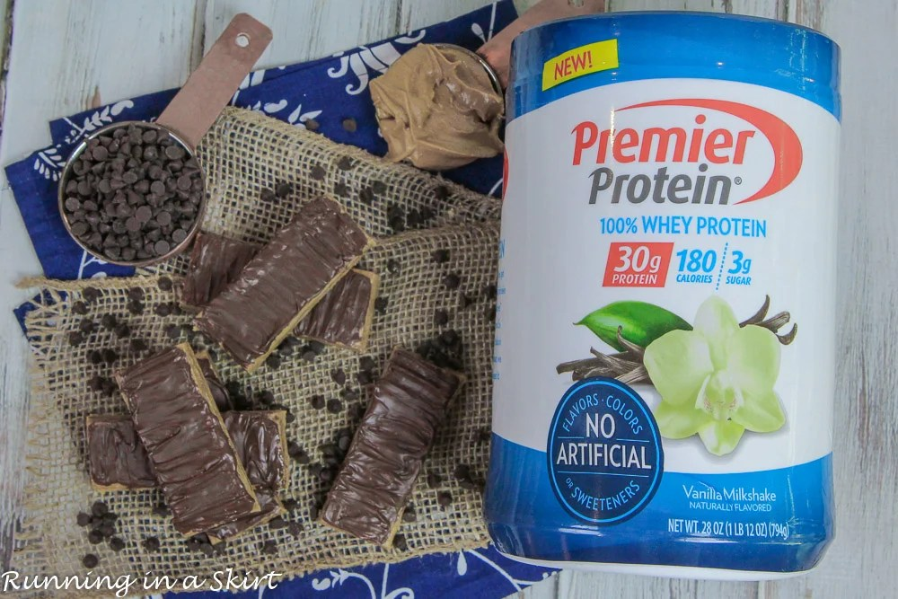 A pile of no bake peanut butter protein bars next to a container of protein powder.