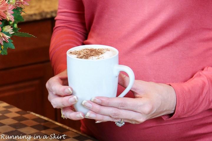 Hands holding mug of dirty chai latte.