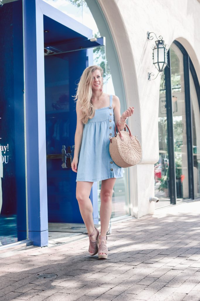 Blonde Dallas Blogger, Running in Heels wears a chambray mini dress with buttons up the front. She carries a straw circle bag and wears pink wedges.