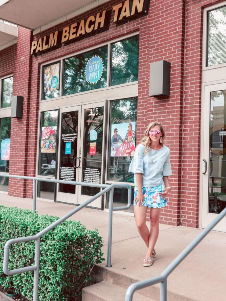 Getting Concert Ready with Palm Beach Tan: Blonde Dallas Blogger, Running in Heels stands in front of Palm Beach Tan in West Village, Dallas, TX wearing chambra flutter sleeve top with tie back, paired with a Lilly Pulitzer scallop hem skort and rose gold glitter keds.
