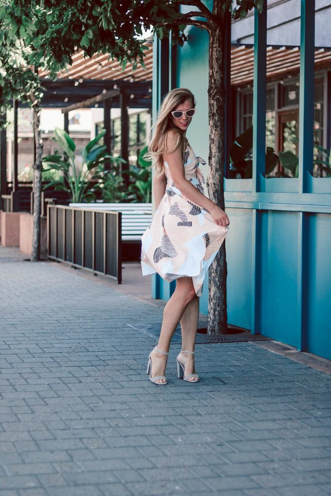 blonde girl wears Geo print, cut-out tie front dress from Forever 21 with nude Steve Madden heels and cat eye sunglasses