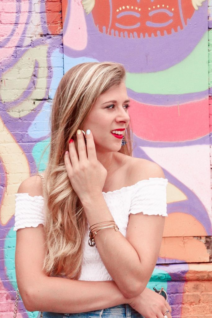 Murals of Dallas | Blonde Girl stands in front of whimsical print mural wearing white crop top and denim mini skirt