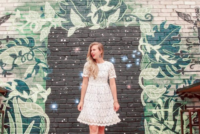 Murals of Dallas | Blonde Girls in crochet dress stands in front of starry sky mural lined with painted vines