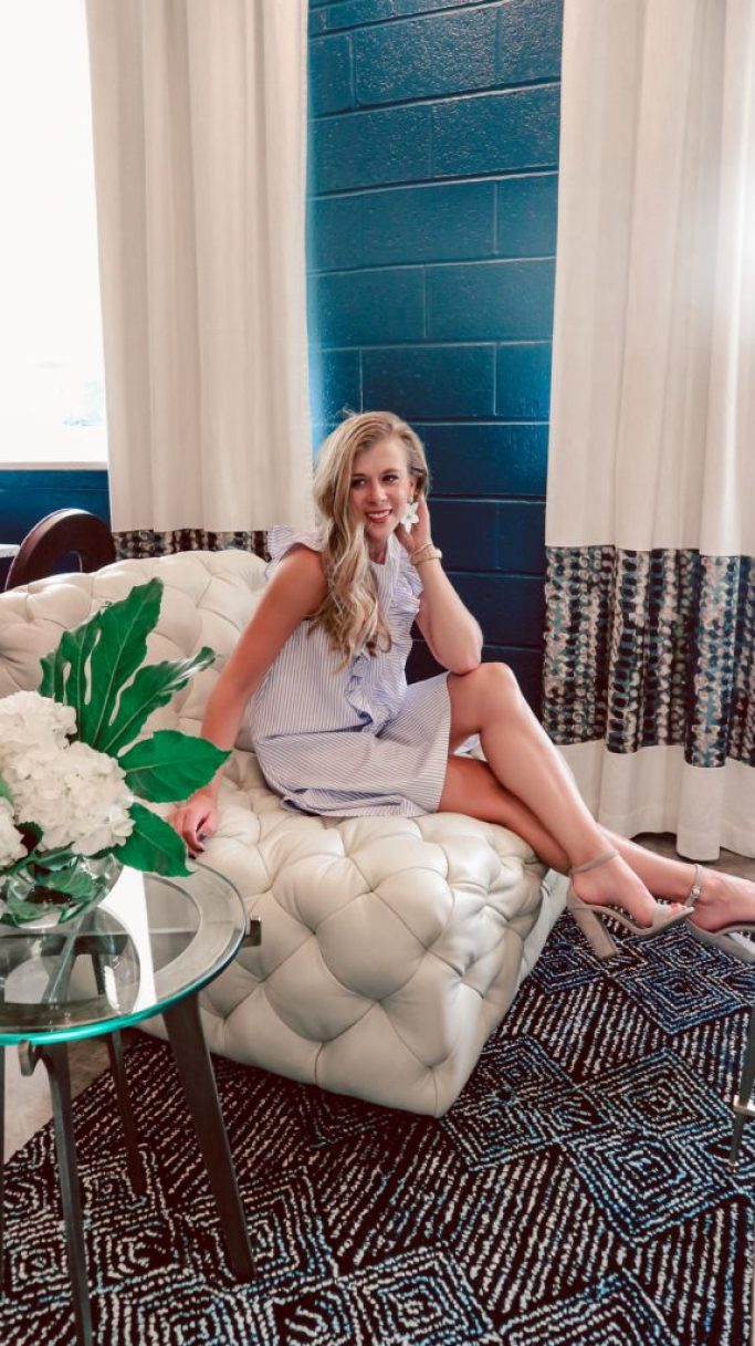 Chijmes, A Dallas Boutique Hotel | Running in Heels | Dallas Blogger sits in lobby of hotel wearing striped dress from she in and flower earrings from Sugarfix