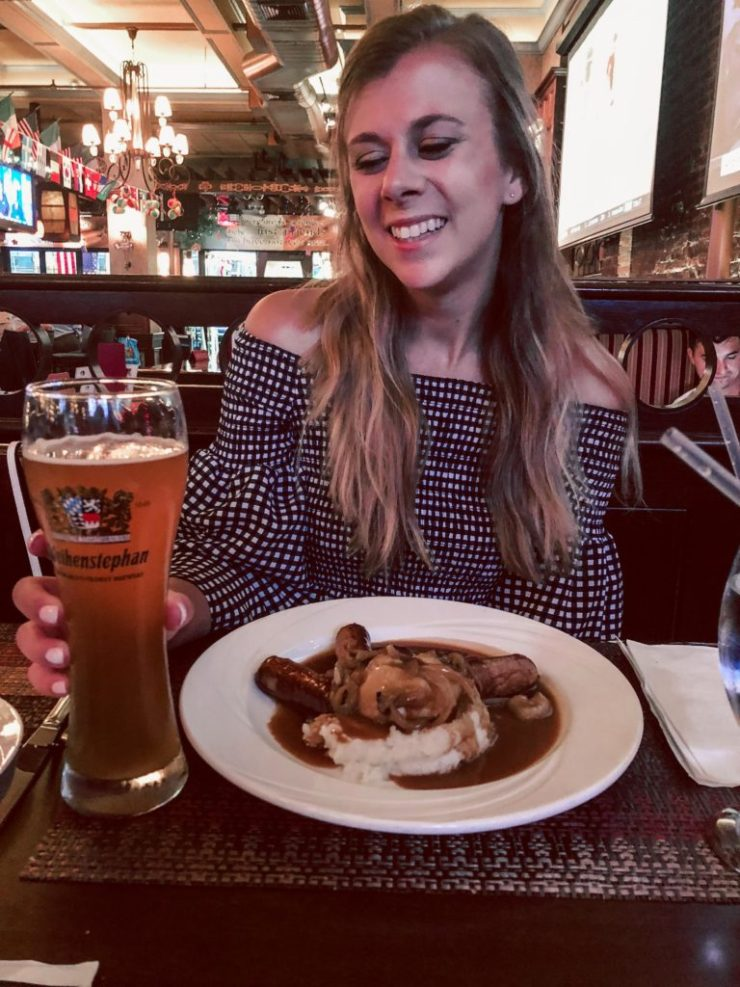 Where to eat in NYC, The Keg Room, girl sits with bangers and mash plus a tall beer in front of her
