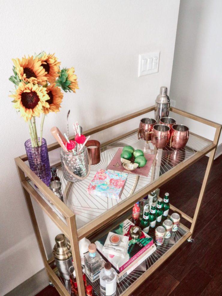 Summer Bar Cart Decorating on a gold bar cart, sunflowers, limes, and coper mugs.