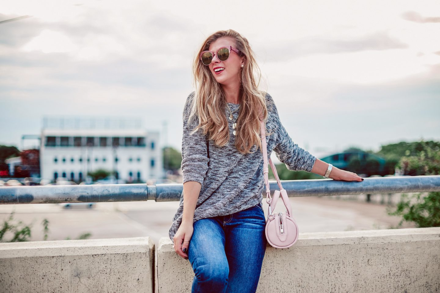 2018 Fall Trends I'm NOT Wearing   blonde sits on bridge in Dallas wearing a grey 3/4 sleeve sweater from Express, blue jeans by DL1961, and DIFF sunglasses. She carries her pink Alexander Wang baby Rockie bag and gold coin baublebar necklace.