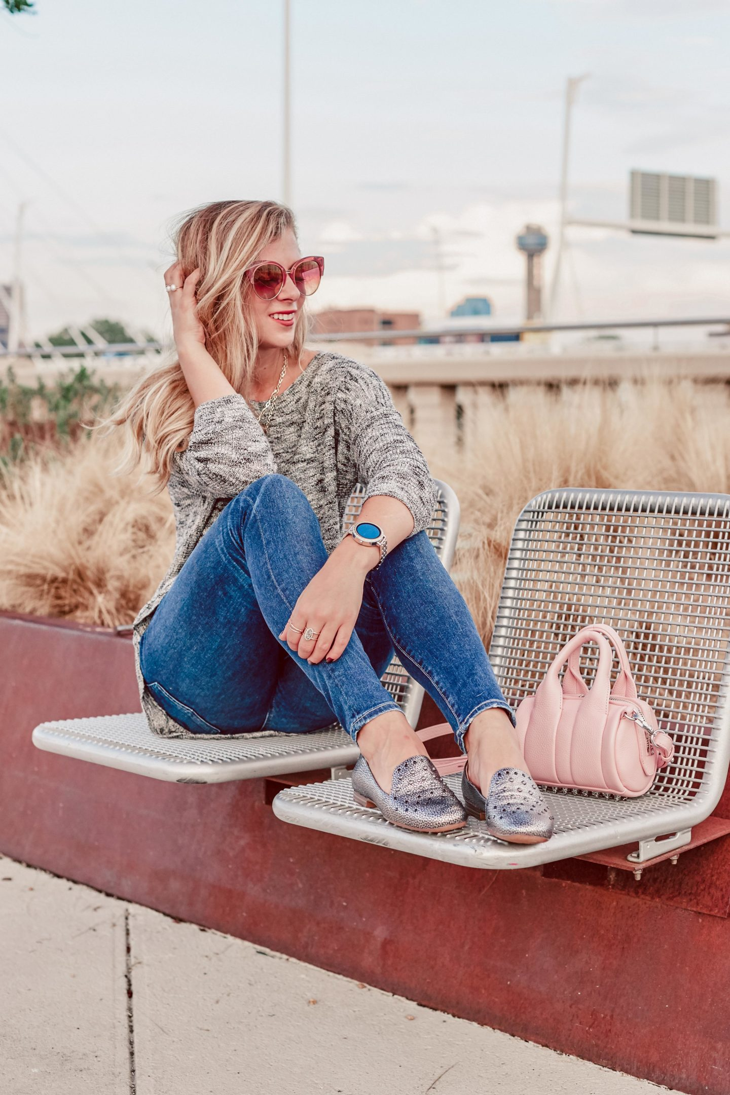 2018 Fall Trends I'm NOT Wearing   blonde sits on bridge in Dallas wearing a grey 3/4 sleeve sweater from Express, blue jeans by DL1961, silver flats called Emmaline by Naturalizer, and DIFF sunglasses. She sits next to her pink Alexander Wang baby Rockie bag.