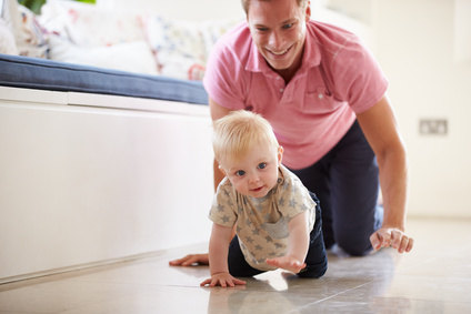 Father And Young Son Crawling Around Room Together