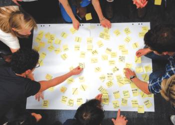 Studenten arbeiten mit Post-Its, um ihre Ideen auf Papier zu bringen. Foto: Andreas Lauenroth