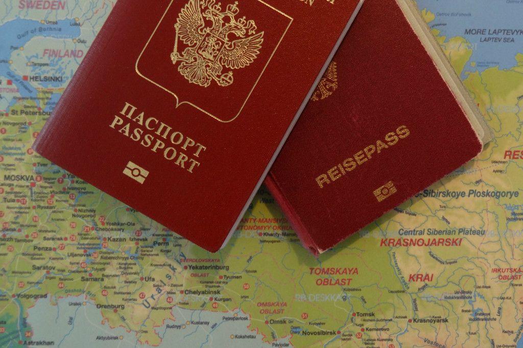 russischer und deutscher Reisepass auf einer Landkarte von Russland