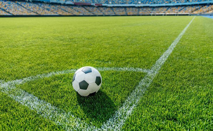 Auf dem Rasen liegender Fussball in einem großen Stadion
