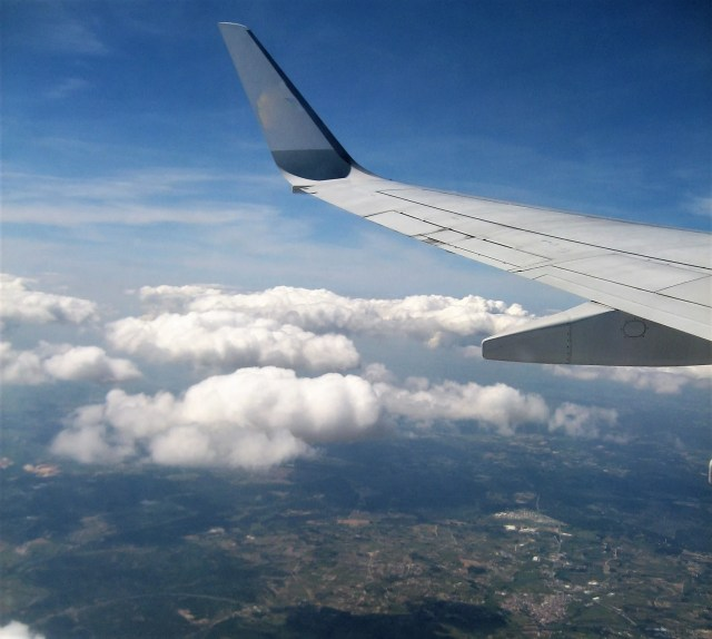 Uitzicht uit een raam van een vliegend vliegtuig. Je ziet vleugel, wolke en de aarde.