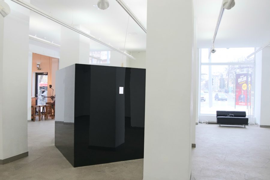 black reflective plexiglass cube with shining screen in gallery space