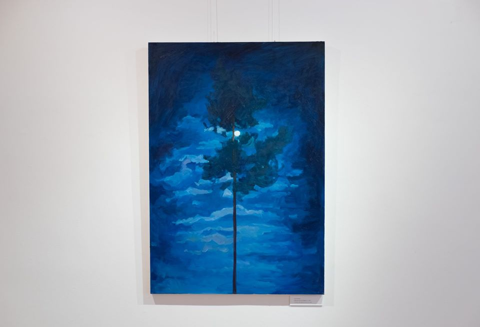 dark tree surrounded by blue clouds at night, moon in the center