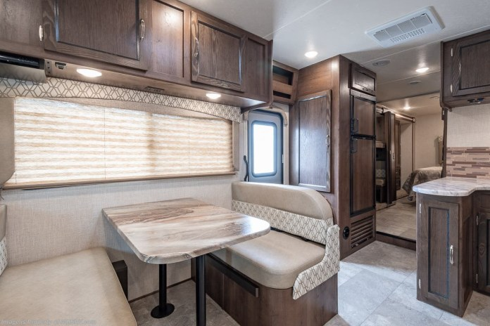 Take a look at this gorgeous kitchen! The perfectly placed lighting, solid countertops and cabinets take the aesthetics of this motorhome to the next level. Enjoy the dining table, residential sized-microwave oven, and large refrigerator for all your favorite meals. And don't worry about where you plan to store your pots, pans, and other essentials. This unit is LOADED with storage areas inside and out for all of your belongings