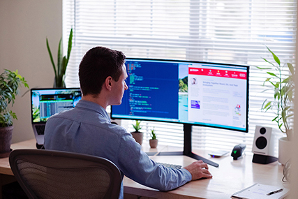 A man working from home in front of a big monitor
