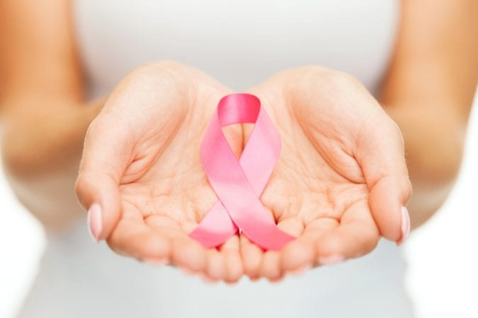 Breast Cancer pink ribbon held out by female hands