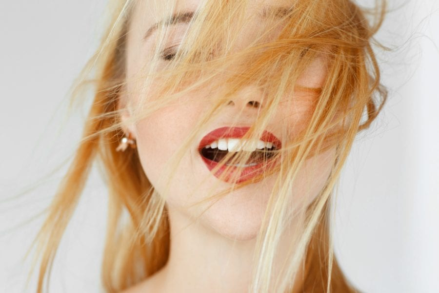 blonde woman hair blowing with red lipstick aroused