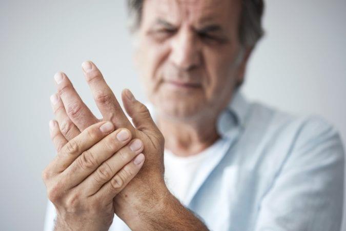 Old Man Holding Arthritic Hand