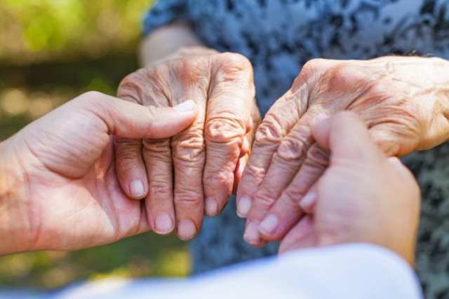 Hands of Parkinson Patient Being Steadied by Doctor
