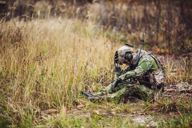 Soldier sitting in field clutching his head