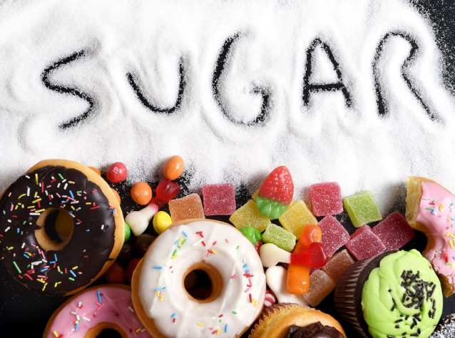 Sugar spilled with donuts, candy and other sugary items spread around