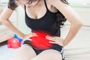 Young Woman with IBS doubled over in pain