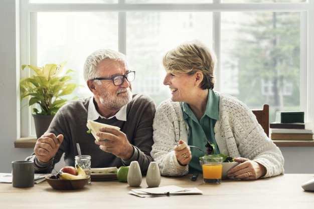 Happy heterosexual elder couple eating breakfast and laughing.