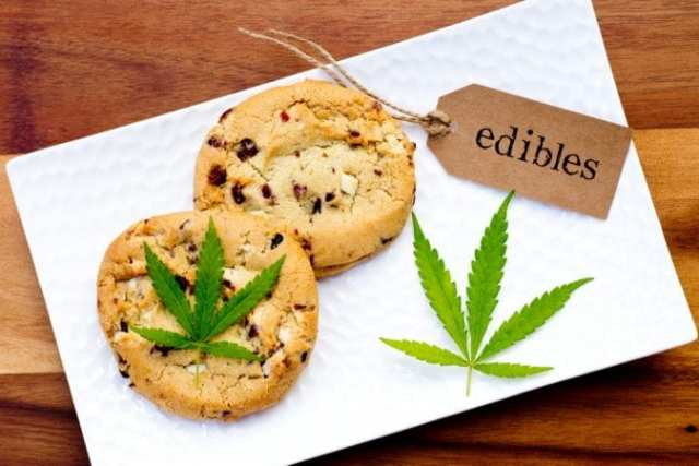 Cookies beside cannabis leaf and edibles sign