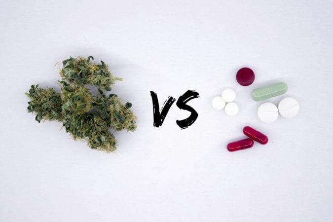 Cannabis bud versus pills on white background