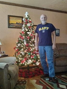 man standing by christmas tree in navy shirt, looking happy - he calims cannabis oil helped him beat cancer
