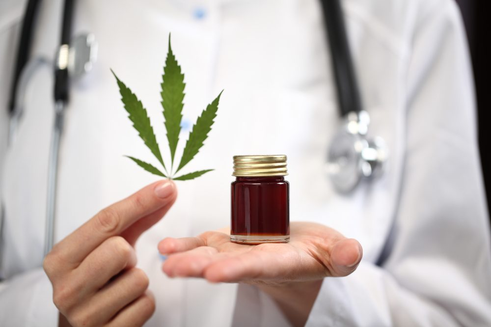 doctor in lab coat holding cannabis leaf and cannabis oil like the kind this man claims helped with his cancer